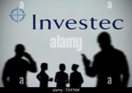 The Investec logo is seen on an LED screen in the background while a silhouetted person uses a smartphone in the foreground (Editorial use only) - Stock Image