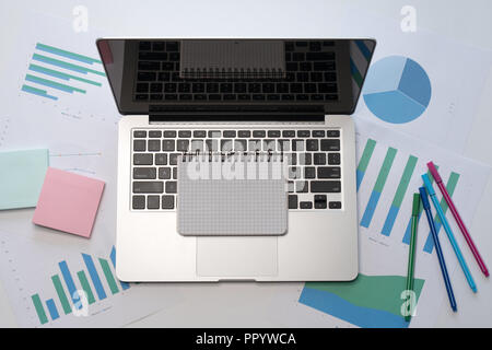 Blank notepad over laptop on office table. Top view with copy space. Desktop with diagrams. - Stock Image