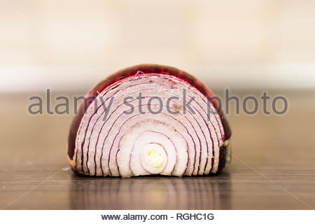 Fresh red onion cut in half on a wooden surface in - Stock Image