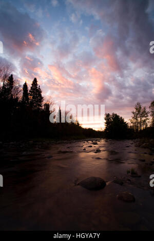 Sunrise lights the clouds above the Nulhegan River in Ferdinand, Vermont.  Northeast Kingdom. Connecticut River - Stock Image
