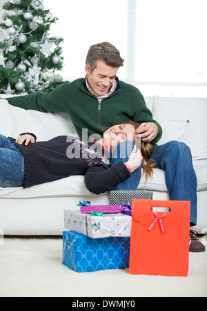Loving Couple With Christmas Gifts Relaxing At Home - Stock Image