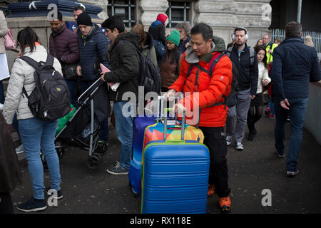A tourist wheels colourful suitcases negotiates the evening rush-hour alongside ordinary commuters at Waterloo Station, on 4th March 2019, in London England. - Stock Image
