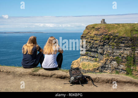 Two young female tourists sit looking out towards O'Brien's Tower and the Aran Islands on the Cliffs of Moher on the Atlantic west coast of Ireland - Stock Image