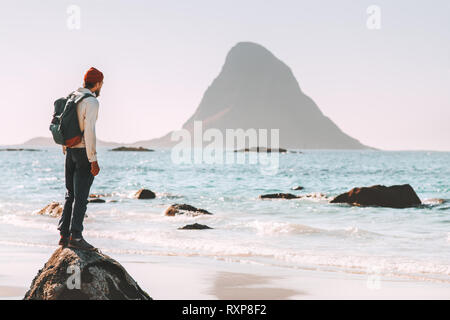 Man tourist enjoying sea and rock view on beach summer traveling in Norway  vacations outdoor lifestyle adventure trip escape solitude emotions - Stock Image