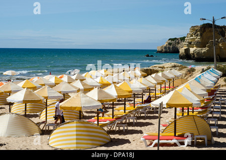 Striped sunshades and beach umbrellas on a blue flag beach in the Algarve - Stock Image