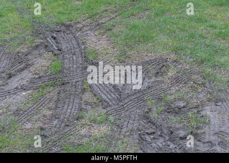 Tyre tracks in soft muddy grass / tracks on grass. - Stock Image