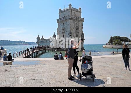 Man with beard & partner take selfies selfie by baby in pram visiting Belem Tower with  tourists outside building in Belem Lisbon Europe  KATHY DEWITT - Stock Image