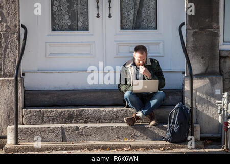 MONTREAL, CANADA - NOVEMBER 4, 2018: Young Caucasian Male, digital nomad, sitting and using his laptop, Apple Macbook, to get wifi internet connection - Stock Image