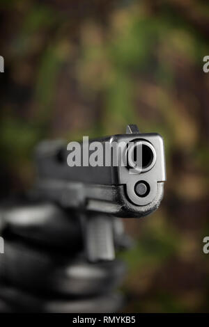 Glock 17 9mm pistol, with camouflage background. - Stock Image