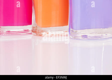 Three multi-colored bright nail polish with reflection - Stock Image