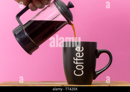 pouring fresh coffee int a mug from a coffee pot - Stock Image