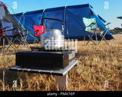 A kettle on a gas camp oven with tents in the background - Stock Image