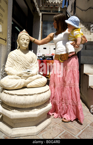 Mother and toddler stroking head of Buddha statue, outside a craft shop in Mijas Pueblo, Costa del Sol, Andalucia, - Stock Image