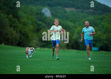 Father and son are running in park with dog english bulldog. Father's Day. Father with son and dog on a walk in the city park on sunny summer day. Fam - Stock Image
