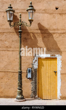 Yellow door and street lamp in the Medina of Marrakech, Morocco - Stock Image
