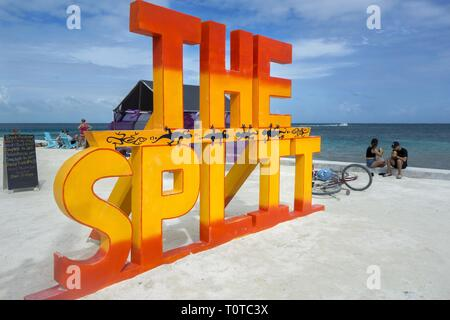 Big Sign on the Beach near Narrow Waterway that divides Caye Caulker, Caribbean Sea Tropical Island in Central America Country of Belize - Stock Image
