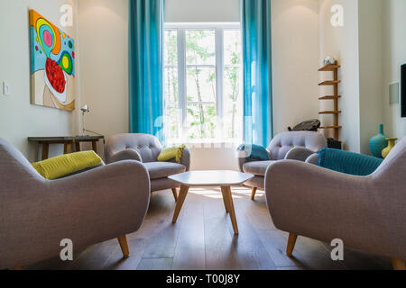 Grey linen upholstered armchairs with wooden three-legged white topped hexagon shaped table in kid's playroom with engineered hickory floorboards - Stock Image