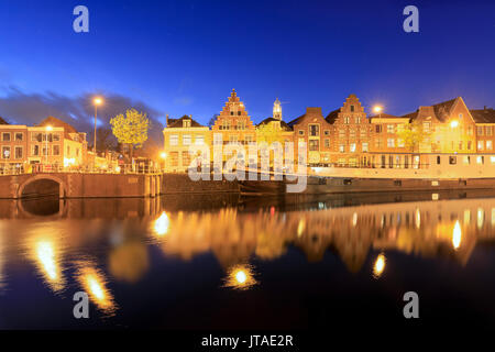 Dusk lights on typical houses and bridge reflected in a canal of the River Spaarne, Haarlem, North Holland, The Netherlands - Stock Image