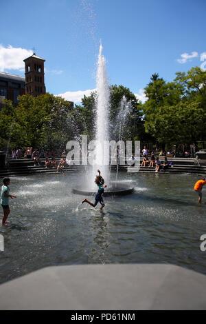 Little girl cools down running through Washington Square Park fountain during summer heat wave in West Village, Manhattan on August 28th, 2014, Manhat - Stock Image