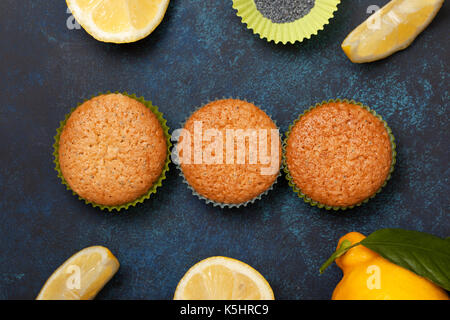 Lemon muffins, fresh lemons on a blue background. View from above. - Stock Image