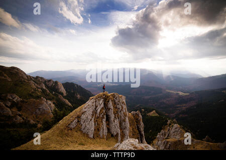 Man standing on cliff against cloudy sky - Stock Image