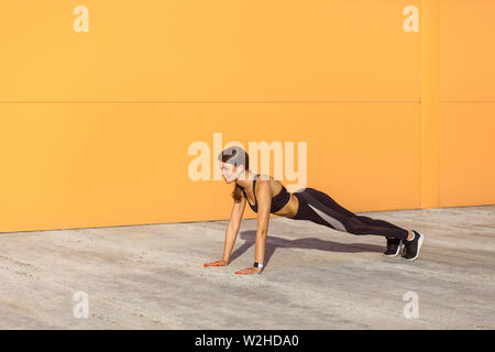 Side view portrait of muscular sporty strong young athletic woman in black sportwear standing on perfect plank position. Outdoor, orange wall backgrou - Stock Image