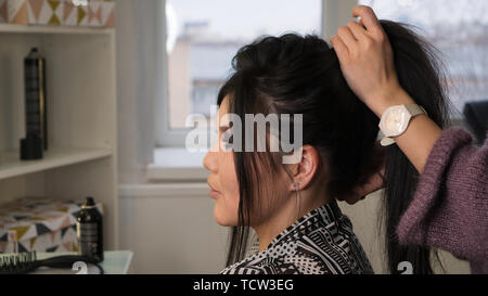 Stylish Pan-Asian in beauty salon. Hands of hairdresser hold hair of client. Hairdressing services. Сreating hairstyle. Hair styling process. Beauty i - Stock Image