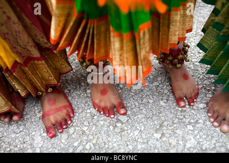 The painted feet of three East Indian or Hindu girls waiting to perform at a festival. - Stock Image