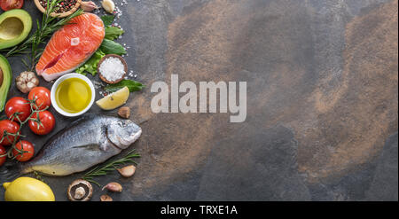 Raw dorado fish and salmon steak with spices and vegetables on the graphite board. Top view. - Stock Image