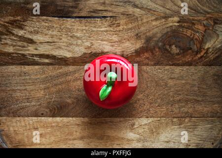 Red, round ceramic apple,flat lay, against wooden board background. - Stock Image