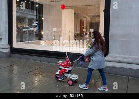 A mother walks past a window display that is part of a design theme called 'State of the Arts', at the Selfridges department store on Oxford Street, on 4th March 2019, in London England. State of the Arts is a gallery of works by nine critically-acclaimed artists in Selfridges windows to celebrate the power of public art. Each of the artists are involved in creating a site-specific artwork at one of the new Elizabeth line stations as part of the Crossrail Art Programme. - Stock Image