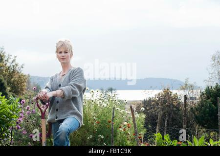 Portrait of mid adult woman digging in organic garden, Orust, Sweden - Stock Image