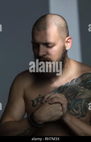 Bare chested man with tattoos - Stock Image