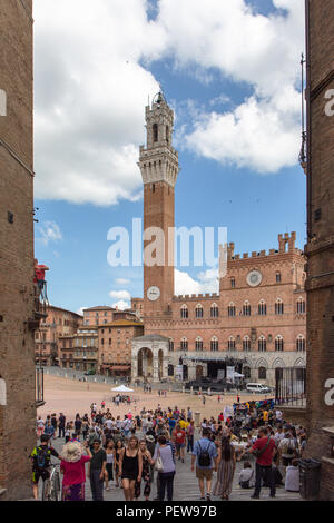 Siena, Italy. Tourists on Piazza del Campo with the Mangia Tower. - Stock Image