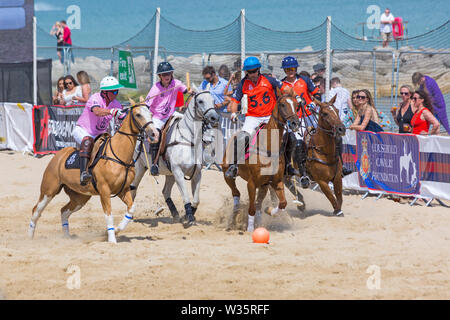 Sandbanks, Poole, Dorset, UK 12th July 2019. The Sandpolo British Beach Polo Championships gets underway at Sandbanks beach, Poole on a warm sunny day. The largest beach polo event in the world, the two day event takes place on Friday and Saturday, as visitors head to the beach to see the action. Credit: Carolyn Jenkins/Alamy Live News - Stock Image
