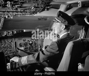 1960s AIRPLANE  PILOT HAND ON CONTROLS IN COCKPIT OF AIRLINE AIRCRAFT - a7301 HAR001 HARS ADVENTURE AIRPLANES PROTECTION KNOWLEDGE OF AIRLINES AUTHORITY AVIATION OCCUPATIONS COCKPIT CONTROLS BLACK AND WHITE CAUCASIAN ETHNICITY HAR001 OLD FASHIONED - Stock Image