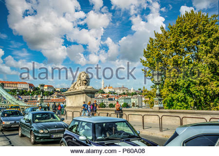 Tourists and locals pass the stone lions as they cross the Danube River on the Széchenyi Chain Bridge with the Budapest Hungary Castle Complex above - Stock Image