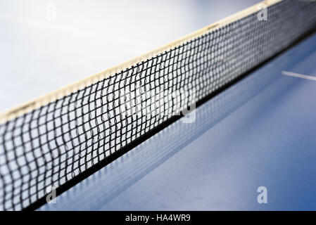 Black mesh tabletennis net in diagonal composition on a blue ping pong table - Stock Image