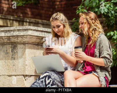 Two female university students sitting together and using their technology outside on the campus; Edmonton, Alberta, Canada - Stock Image