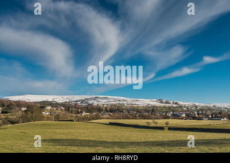 North Pennines AONB Landscape, Middleton-in-Teesdale with snow covered fells in the background and a large cirrus cloud formation overhead - Stock Image