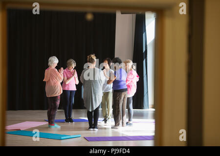 Serene active seniors practicing yoga in circle - Stock Image
