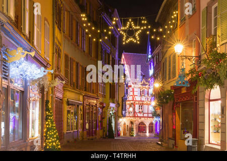 Traditional Alsatian half-timbered houses in old town of Colmar, decorated and illuminated at snowy christmas night, Alsace, France - Stock Image