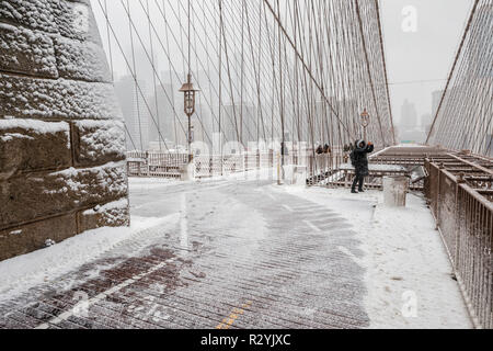 Brooklyn Bridge at snow storm, a view to Manhattan buildings in fog - Stock Image