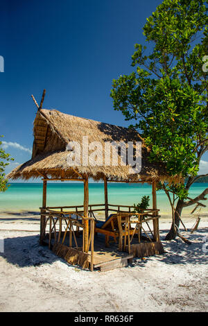 A paradise island beach shade hut and sun loungers on a white sand beach with beautiful turquoise sea. - Stock Image