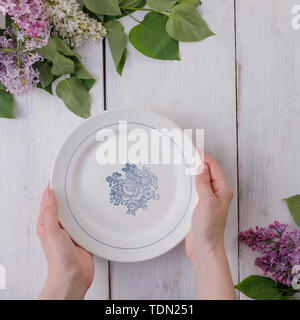 A plate and a decor of flowers on a background of white-painted wooden boards. Vintage background with lilac flowers and a place under the text. View  - Stock Image