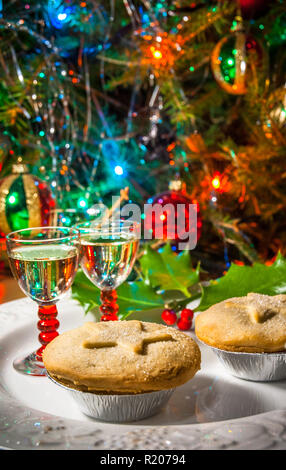 A festive plate of mince pies and sherry with Christmas tree and lights. - Stock Image