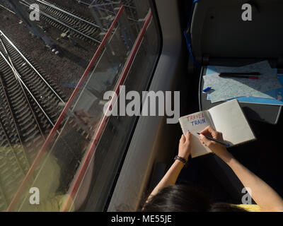 blogging during journey in diary book writing words travel train with maps liying on the table copy space - Stock Image
