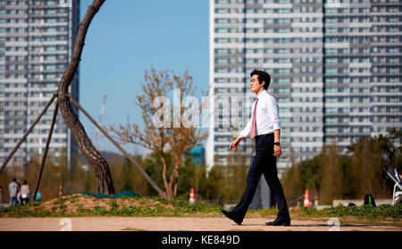 Side view of businessman taking a walk at park - Stock Image