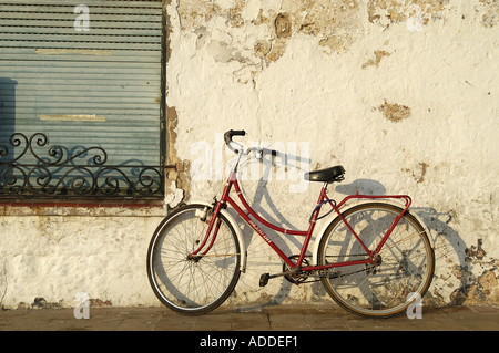 A red bike leaning against an old, chipping wall. - Stock Image