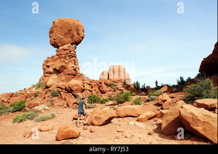 Visitor walking by Balanced Rock, a famous rock formation at Arches National Park, Utah, USA. - Stock Image